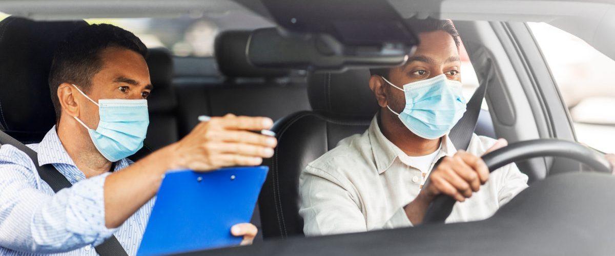 Fahrlehrer und Fahrschüler mit Medizinmaske im Auto